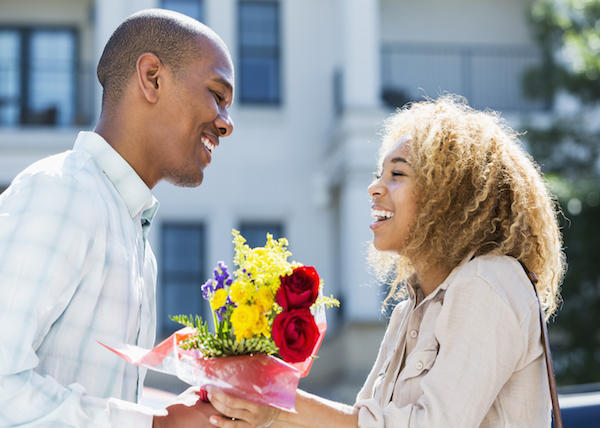 Man giving a bouquet of flowers to his partner.